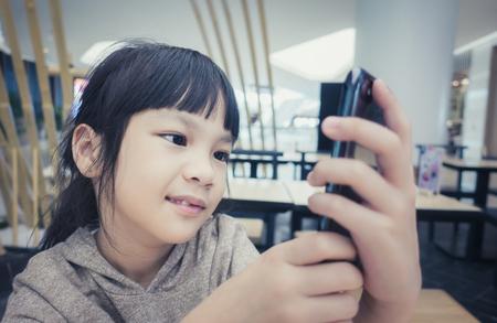 Asian kid is talking on speaker phone in cafe