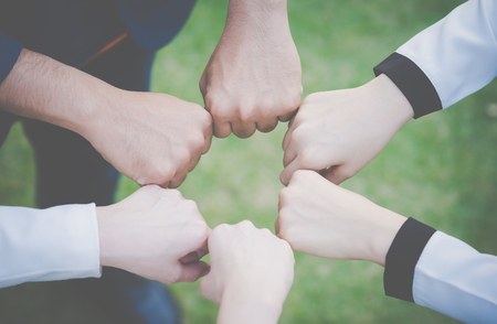 Team fist bump together to form team spirit concept