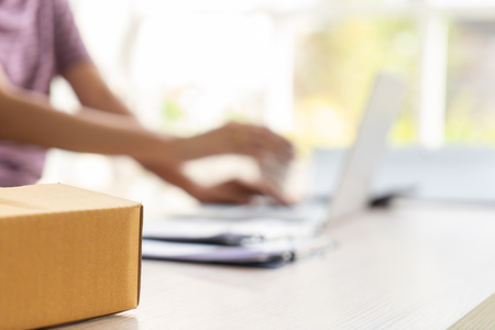 business woman sitting in a desk full of delivery boxes Stock Photo