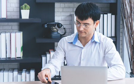 Modern Business man is busying using laptop and smartphone.