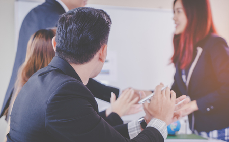 Co worker clapping to celebrate success of business team mate