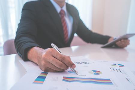 Business man marking on data sheet using metal pen Banque d'images