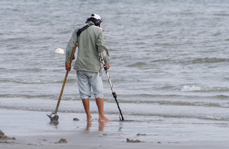 Pattaya, Thailand - May 10, 2018: A man is using metal detector to find coin on a beach.