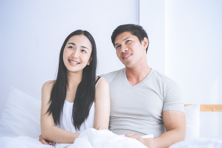 Happy Asian couple looking up on bed Stockfoto