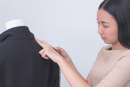 Female tailor is measuring a gentlement suit jacket