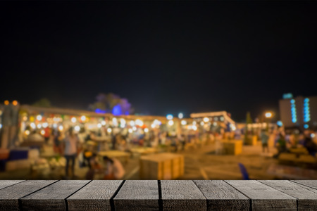 Empty wooden shelf display with night market background