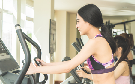 Asian woman is working out in fitness gym machine