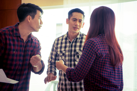 Friend trying to stop team from anger discussion Stock Photo