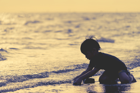 Boy facing out to the sea on a Vacation Beach holidays silhouette 写真素材