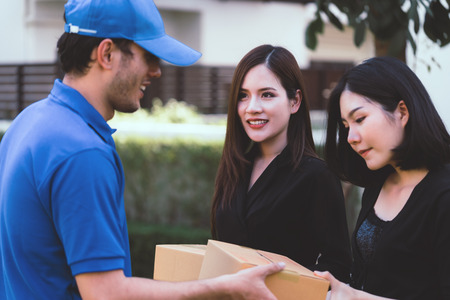 Delivery man in blue is handing packages to two woman