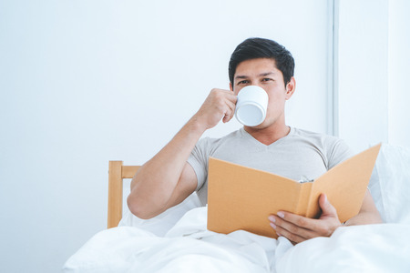 Asian male is reading book and drink coffee on morning bed