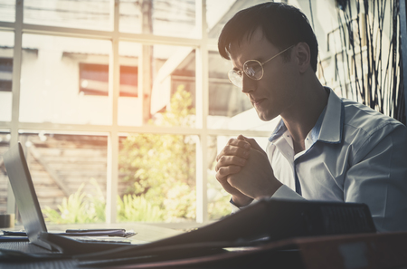 Business man is praying for business on computer