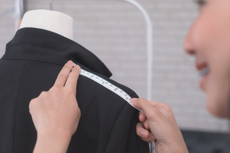 Female Tailor is measuring jacket with measuring tape