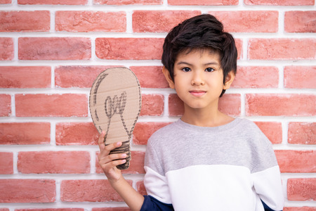 Kid holding paper bulb for idea concept
