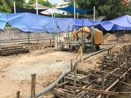 Starting pouring wet concrete in to a house foundation construction site