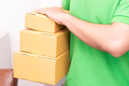 Delivery man in green is handing packages Stock Photo - 105265470