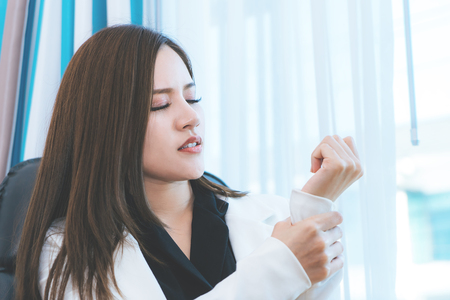 Female office worker is having office syndrome injury on her wrist Stock Photo