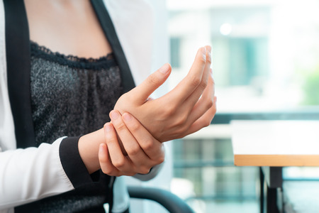Female office worker is having office syndrome injury on her wrist 스톡 콘텐츠