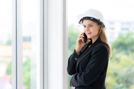 Female engineer is making call in office building
