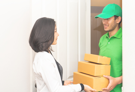Delivery man in Green is handing packages to a woman door Stock Photo - 106462340