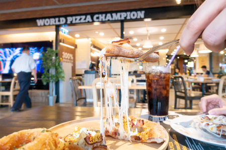 Bangkok, Thailand - June 17, 2018: Customer is cutting pizza out in Mr.Pizza  Thailand world champion restaurant.