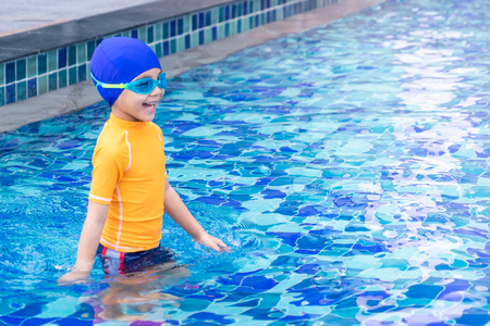 Wet suit swim Asian boy is standing on pool side