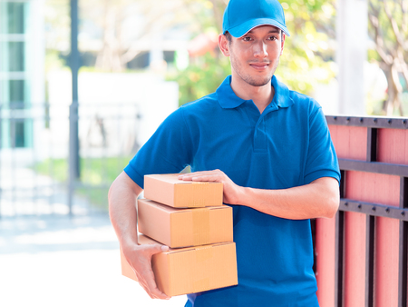Delivery man in blue is handing packages
