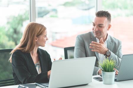 Mannelijke baas bespreekt op een gelukkige manier met vrouwelijke werknemer Stockfoto