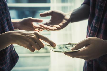 Business man hands handing money over a business dealing Standard-Bild - 105586219