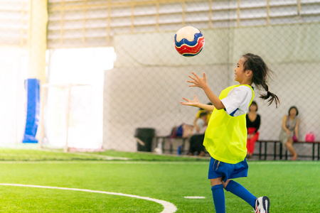Little Asian girl is training in indoor soccer field Stock Photo
