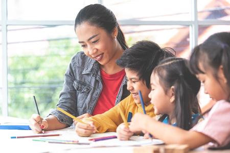 Asian Teacher is teaching children in kindergarten classroom