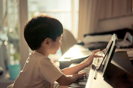 リトル・ボーイズは自宅でピアノと音楽タブレットで演奏しています
