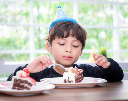 Kid with party hat is eating birthday cake Stock Photo