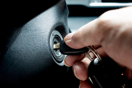 Hand turning car key in the key hole to start the car engine