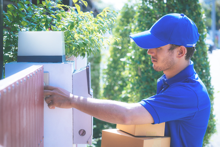 Delivery man in Blue is handing packages to home Stock Photo