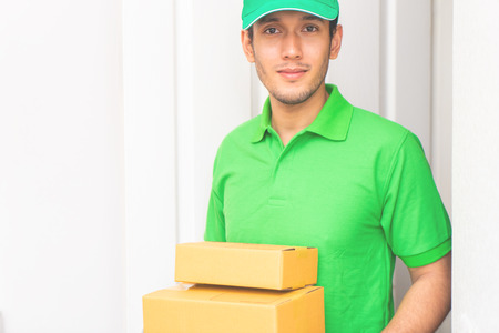 Delivery man in Green is handing packages to your door Stock Photo - 106823954
