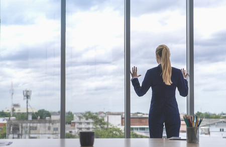 Female business woman is looking out the windows for success Stock Photo