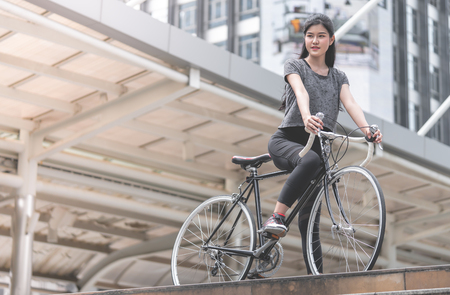 Sport woman is posting with her bike on the stair