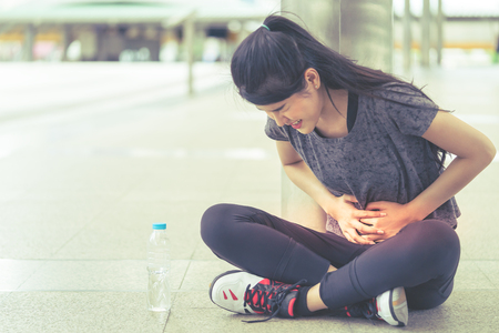 Sport woman is having an injury on her stomachache peroid Reklamní fotografie