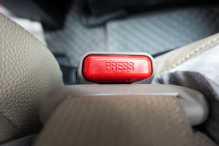 pressing and releasing button seat belt buckle in car