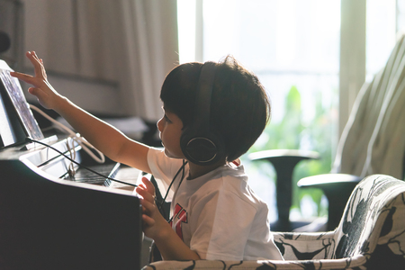 Little Boy is playing with piano and Music Tablet at home Foto de archivo - 107680302