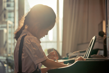 Little girl is playing with piano and Music Tablet at home Foto de archivo - 107680303