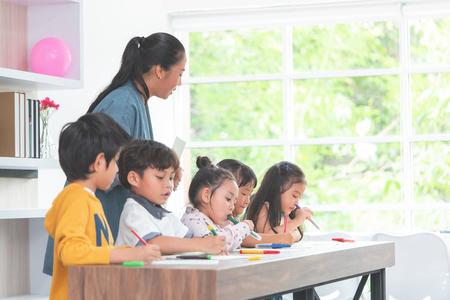 Maestro asiático está enseñando a los niños en el aula de jardín de infantes Foto de archivo