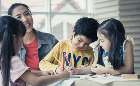 Asian Teacher is teaching children in kindergarten art classroom