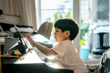 Little Boy está jugando con el piano y la tableta musical en casa