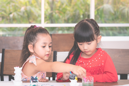 Asian girl is painting a doll in Art classroom
