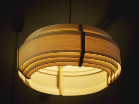 Orange ceiling lamp in dark room. Stock Photo