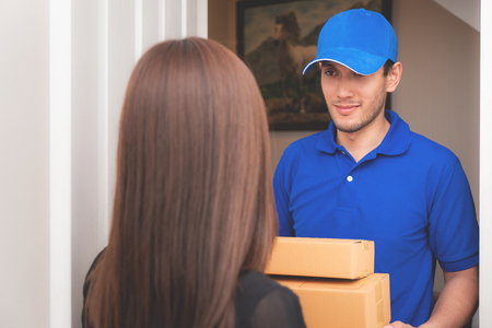 Delivery man in Blue is handing packages to a woman door