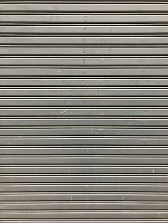 Gray Rustic store retail metal gate wall closed.