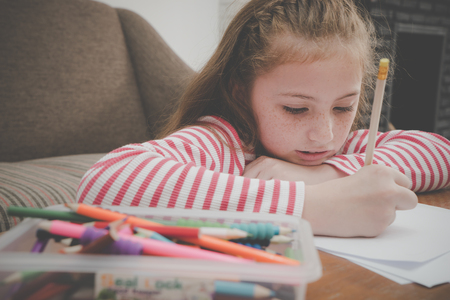 Little girl is coloring on blank paper in living room